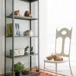 El tapete del estudio es un dhurrie marroquí. La silla, de diseño tipo francés, es de hierro, al igual que la biblioteca con rejilla metálica en los costados. Los pájaros de madera, junto a los libros, el baúl y la caja circular de níquel, decoran el espacio en el que la planta complementa con su tono verde.