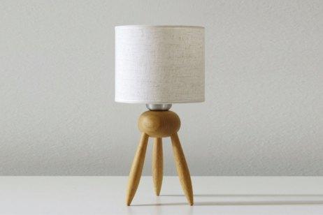 Trípode. Lámpara en madera clara torneada. Tiene líneas simples que ayudan a subrayar la calidez del material. Es un modelo todo terreno, que resulta un excelente complemento tanto para un dormitorio como para un estar. (Castelar Iluminación).