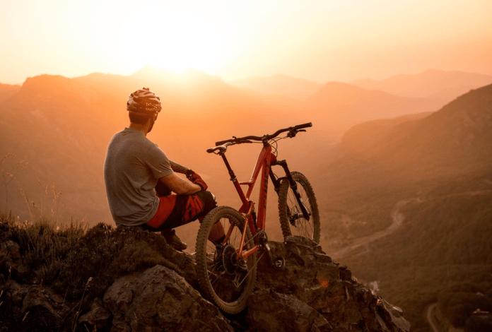 Um ciclista desfruta do pôr do sol.