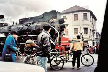 Trem a vapor atravessando uma estrada no distrito de Hankou na década de 1990. Crédito: http://en.hubei.gov.cn/photo_gallery/scenery/201505/t20150508_652298.shtml