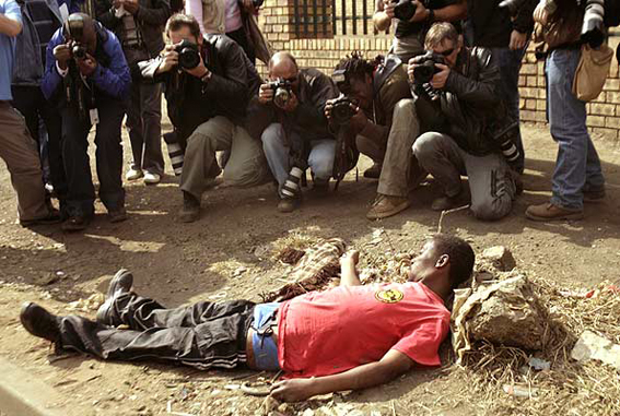 Periodistas fotografían a un hombre herido durante los disturbios en Reiger Park, Sudáfrica, en 2008. Foto © Siphiwe Sibeko / Reuters. www.20minutos.es