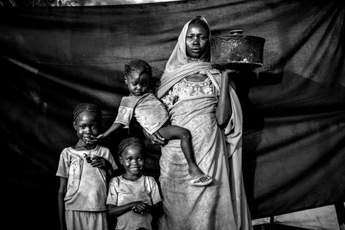 La olla que Magboola sostiene en la fotografía fue lo único que pudo rescatar de sus pertenencias. En ella cocinó el sorgo que las alimentó durante la travesía. Foto © Brian Sokol.
