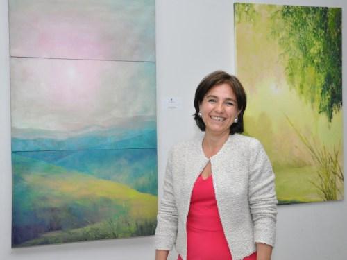 La pintora María Claudia López posando con algunas de sus obras.