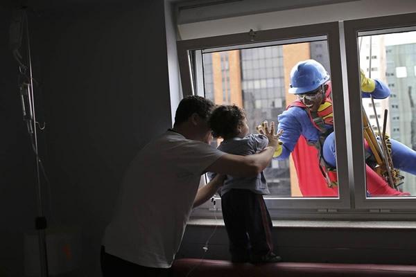 Las Imágenes más Sobrecogedoras de 2013 - Un limpiacristales vestido de Superman en el Hospital infantil Sabara en Sao Paulo, Brasil.