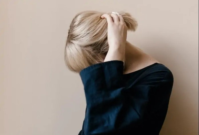 woman in blue shirt covering her face with her hair