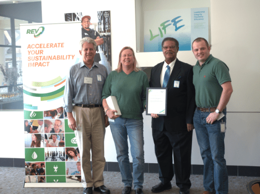 Sims Metal receives their certificate of completion from Nathaniel Bates, Councilmember of Richmond.