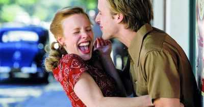 Photo du film N'oublie jamais : Allie et Noah se chamaillent en pleine rue. Elle porte une robe rouge et lui une chemise kaki.