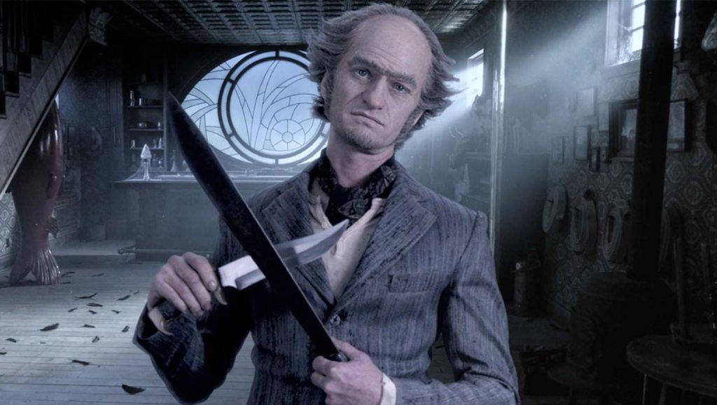 Cette image présente le Comte Olaf, dans le grenier de sa maison, aiguisant son couteau de cuisine, vêtu d'un costume gris. La fenêtre de la mansarde a la forme d'un oeil intrigant.