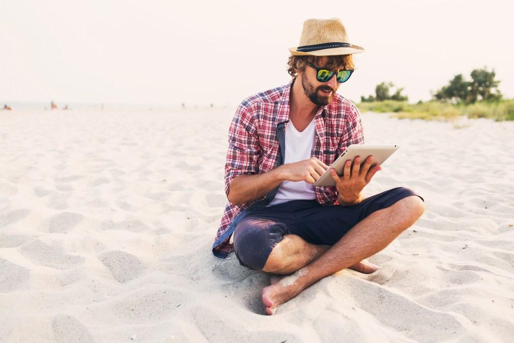 Un homme en tailleur sur la plage avec sa tablette