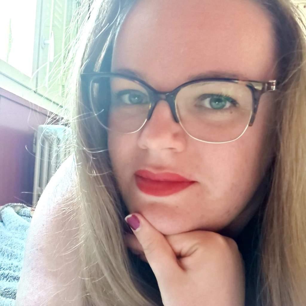 Coline Wylandriah Nephtys est une jeune femme blonde aux yeux bleus, qui porte des lunettes rondes et noires.