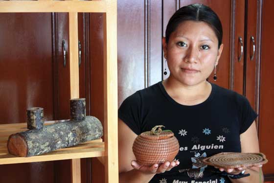 Rossmery Jocón displays a candleholder and some of the pine-needle típico of Corazón del Bosque.