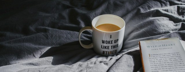 "Tasse ""I woke up like this #tired"" sur un drap froissé"