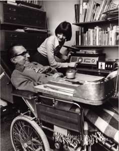 A man sat in a wheelchair with a desk attached in an office, with a woman helping him to use an adapted telephone