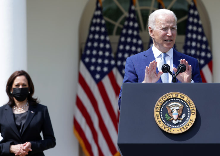 [PHOTO: Kamala Harris wears a dark suit and mask in the background. Joe Biden in a blue suit in the foreground speaking behind a podium]