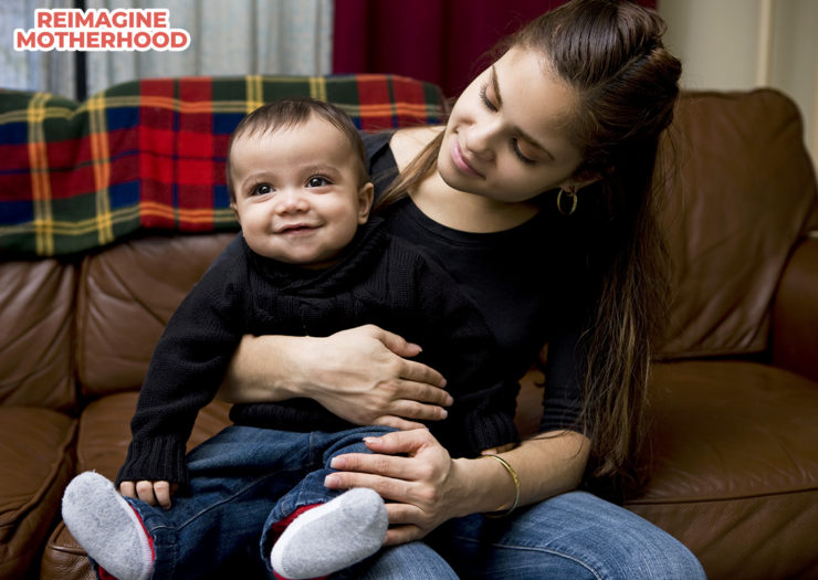 [PHOTO: Boy sitting on young mother's lap]
