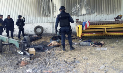 Federal police stand near the bodies of men who authorities say were suspected cartel gunmen at the Rancho del Sol, near Ecuanduero, in western Mexico, Friday, May 22, 2015. At least 43 people died Friday in what authorities described as a fierce, three-hour gunbattle between federal forces and suspected drug gang gunmen at the ranch. (AP Photo/Oscar Pantoja Segundo)