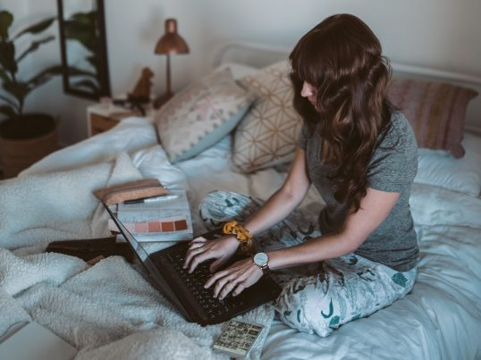 Woman studying in bed - How to cope with stress - RGU Student Blog