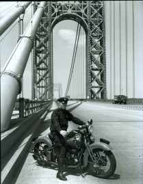 "One of the new officers assigned to the George Washington Bridge Command sits astride a Harley Davidson ""Knucklehead"" motorcycle."