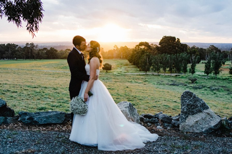 The bride & groom share a kiss in front of the sunset, taken by a perth wedding photographer.