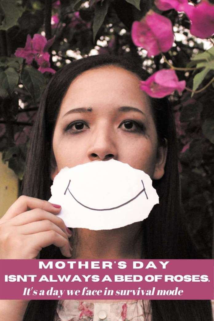 Mother's Day, Loss, grieving, surviving Mother's Day, sad woman standing in front of flowers with a piece of paper over her mouth with a smile drawn on it
