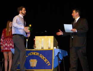 Ryan Quirk receives his brother Jared's NHS senior certificate from RHS Principal, Dr. Cron.