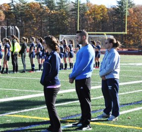 Rockland coaches, Lauren Rizzotti, and Ronnie Ricciarelli along with Cohasset coach, Deb Beal stand for the National Anthem.