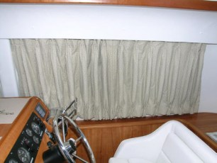 Pinch-pleated curtains with tie backs at helm station