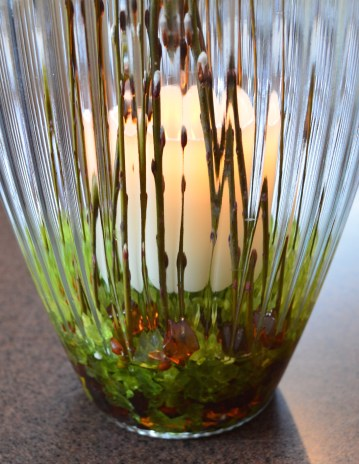 Close up of candle and pussy willows in a vase.
