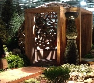 Entrance of a wooden circular pergola made of recycled wood.
