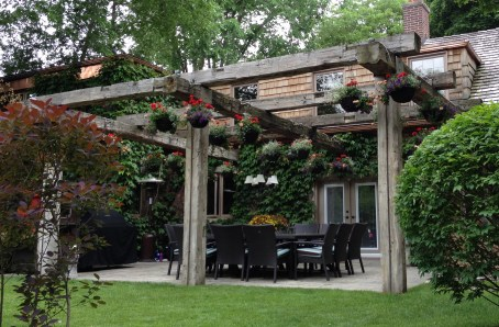 A large pergola overhangs a patio with dining area.