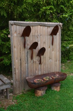 A wooden freestanding panel in a garden showcases old shovels.