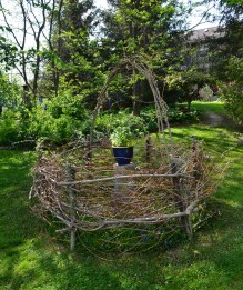 A sculptural basket is made from live willow branches in a garden setting.