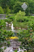 A pond, fountain and bridge with a kinetic sculpture in the background