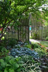 A large trellised archway leads from one garden into another.