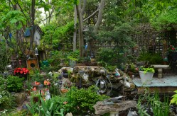 The garden is so densely packed with trees, shrubs, decorations and trellises that you can't see the edges of the very small garden.