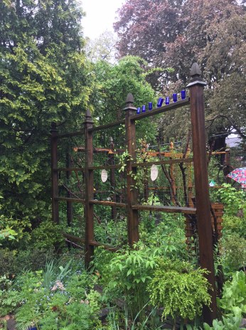 Fanciful fencing creates rooms in a filled back garden.