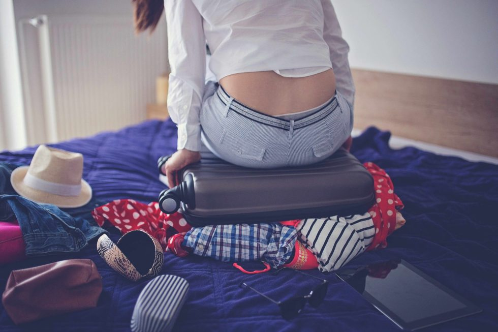 Young woman having trouble packing suitcase bag, not ready, isolated indoors room background, trying to close the suitcase alone, by sitting on it. Rear view.