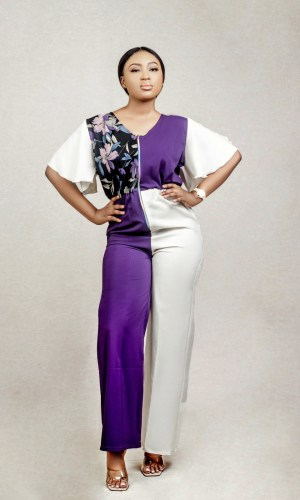 lady posing in a floral blouson jumpsuit with slit sleeves by Ria Kosher