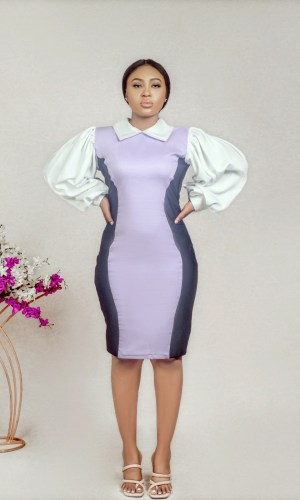 a model standing at akimbo in lilac collared illusion sheath dress by Ria Kosher