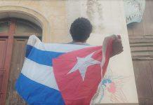 El artista Luis Manuel Otero Alcántara sostiene una bandera cubana frente a una cámara de vigilancia policial