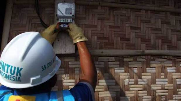 Petugas PLN memasang meteran listrik