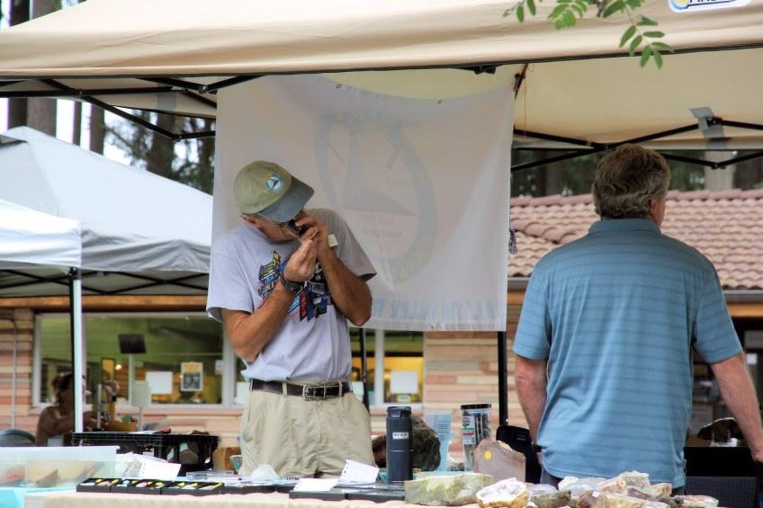 Vendor inspects a rock specimen closely.