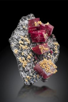 A photo of the Alma Rose rhodochrosite specimen, it is a black rock with gray and yellow crystal formations and 6 large rhodochrosite cubes. Featured on a black background.