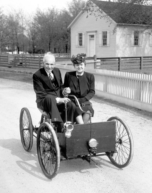 Henry Ford sits beside Clara at the tiller of his Quadricyle in June 1946 on the fiftieth anniversary of its inaugural run. The car is on a quiet street in Ford's museum village; beyond the farmhouses and their picket fences, a remade world clamors along the thoroughfare its inventor built.
