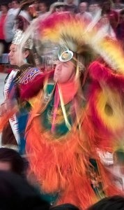 Indoor image at a pow wow, an example of a somewhat long shutter speed, about a 1/15th of a second, used to illustrate motion