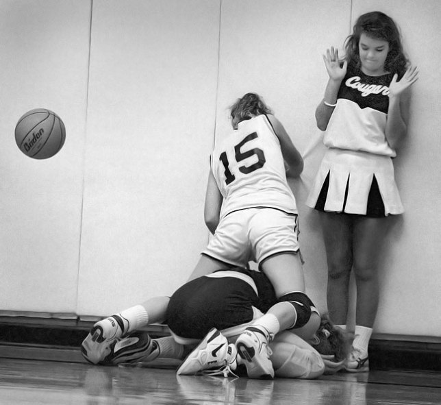 An Ada Lady Cougar basketballer dodges another player and a cheerleader, 1991