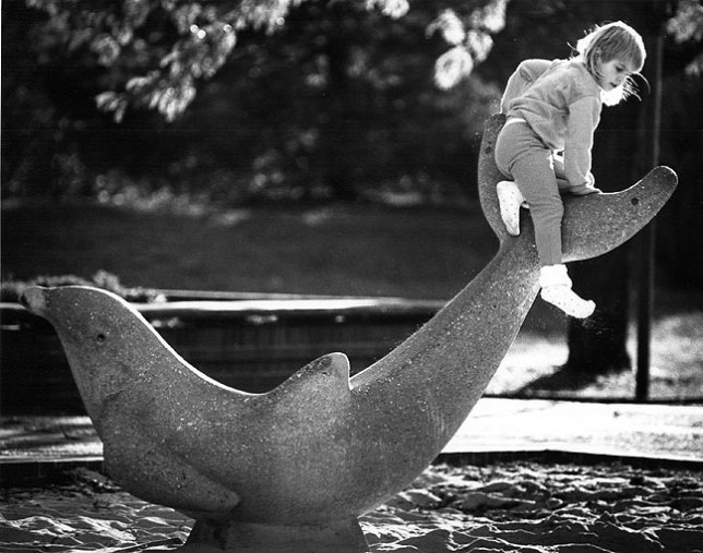 A child plays on a concrete dolphin, 1988