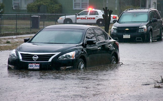 Oops. A car sits stranded in floodwater on Ada's west side this morning.