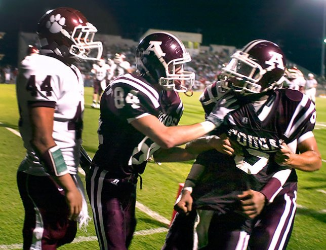 Ada Cougar football players hold their quarterback after words were exchanged with the opposition at the end of a play, September 2008.