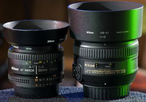 The AF Nikkor f/1.8D, left, sits next to its replacement, the larger and more modern AF-S Nikkor 50mm f/1.4G.